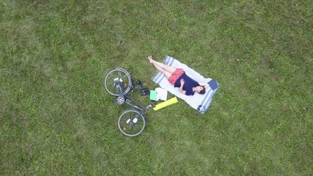 junge frau ruht in einem öffentlichen park - luftbild - liegen stock-videos und b-roll-filmmaterial