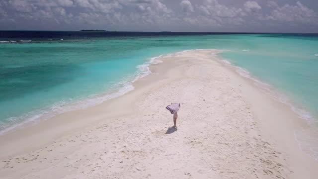 vídeos de stock, filmes e b-roll de mulher adulta nova que funciona em um sandbank de encontro à água de turquesa em maldives - toalha de praia