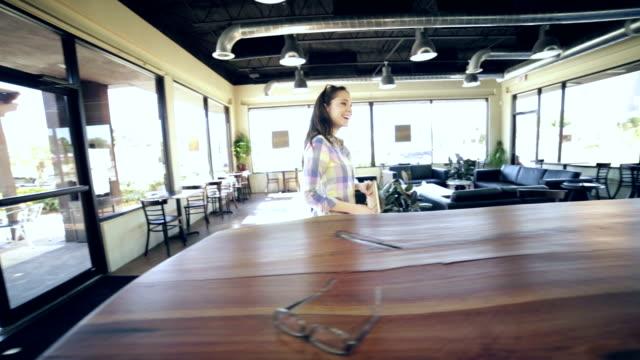 Junge Erwachsene Frau, die Hände schütteln mit Freund oder manager in der coffee shop