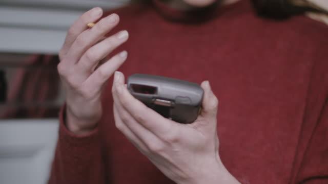 vídeos de stock e filmes b-roll de young adult woman signing for parcel at home - carteiro
