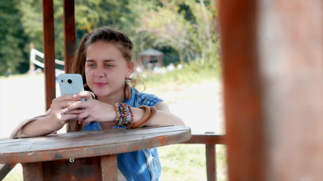 young adult woman sitting in an alcove outdoors and using her smart phone - sleeveless top stock videos & royalty-free footage