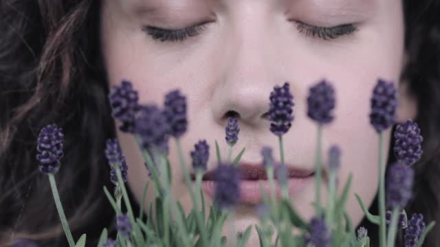 young adult woman smelling lavender - augen geschlossen stock-videos und b-roll-filmmaterial