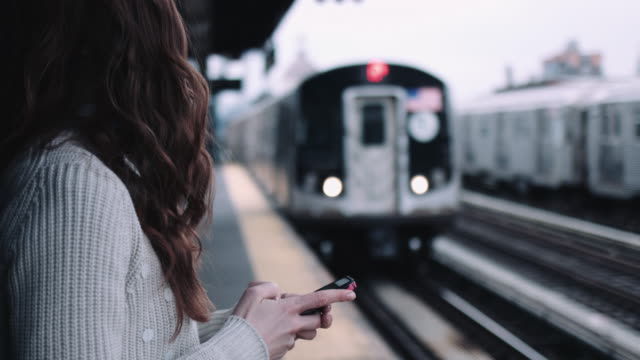 Young adult woman subway platform holding mobile phone