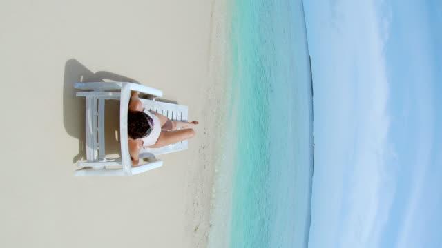 vídeos y material grabado en eventos de stock de joven mujer adulta tomando el sol en la playa - maldivas - dharavandhoo island - bronceado