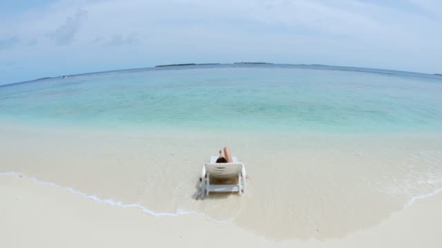 young adult woman sunbathing on the beach - maldives - dharavandhoo island - turquoise coloured stock videos & royalty-free footage