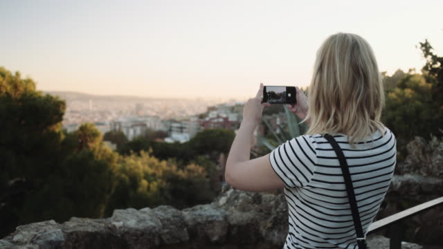 vidéos et rushes de young adult woman taking picture on mobile phone in barcelona - spain