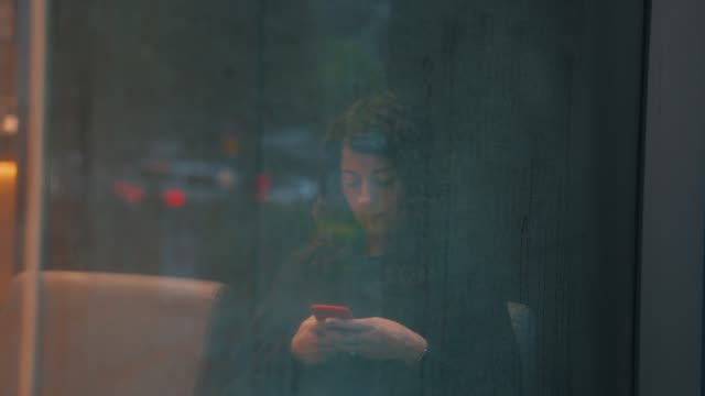 young adult woman texting with smart phone near a window wet by rain - window display stock videos and b-roll footage