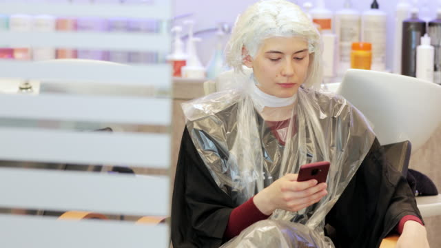 young adult woman using mobile phone while at hair salon - beauty salon stock videos & royalty-free footage