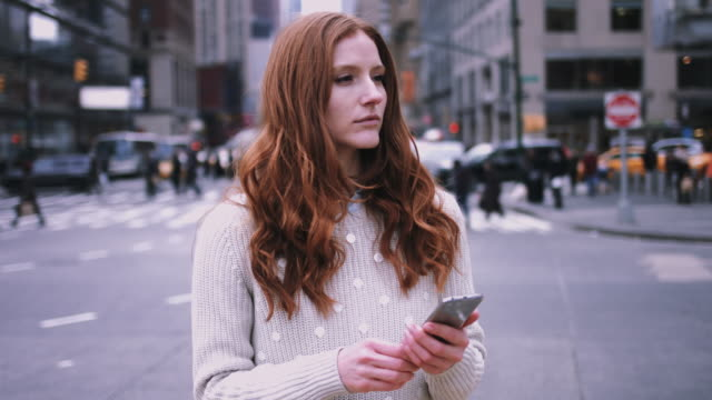 Young adult woman waiting and looking at smart phone on street