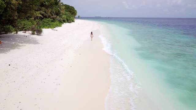 young adult woman walking on a paradisiac beach in maldives - island stock videos & royalty-free footage