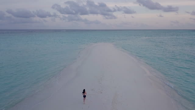 young adult woman walking on a sandbank against turquoise water in maldives - turquoise colored stock videos & royalty-free footage