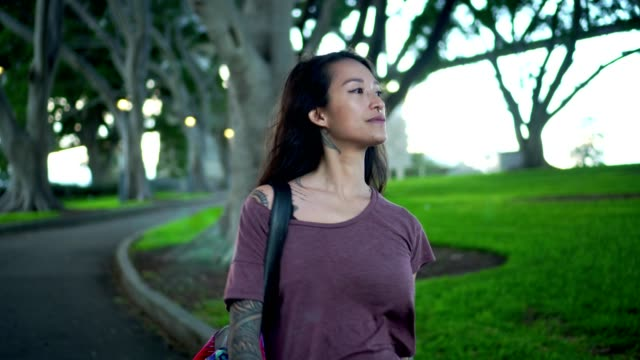vidéos et rushes de jeune adulte femme marchant dans le parc public à côté de l'harbour bridge de sydney - trentenaire