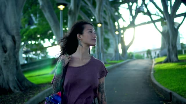 vidéos et rushes de jeune adulte femme marchant dans le parc public à côté de l'harbour bridge de sydney - tatouage