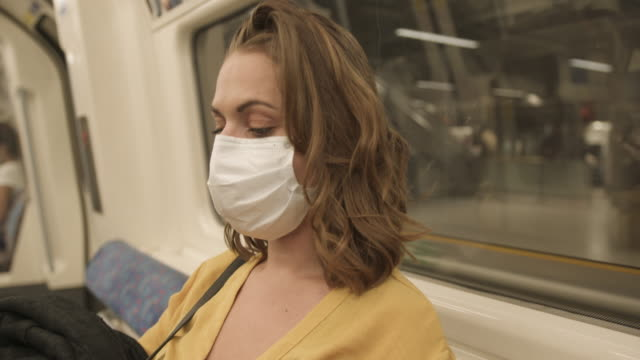young adult woman wearing protective medical face mask on underground train using mobile smart phone during coronavirus pandemic - underground train stock videos & royalty-free footage