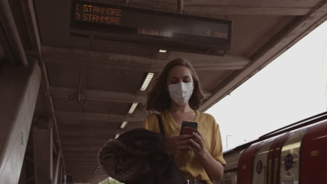 young adult woman wearing protective medical face mask standing on underground train platform waiting and using mobile smart phone during coronavirus pandemic - underground station platform stock videos & royalty-free footage