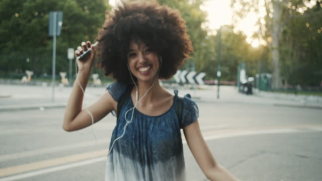 young adult woman with afro hair dancing in the city at sunset while listening to music - pierced stock videos & royalty-free footage