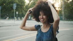 Young adult woman with afro hair dancing in the city at sunset while listening to music