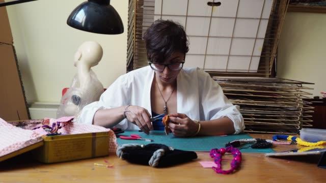 Junge Frau arbeitet an der Schaffung von einigen Halsketten