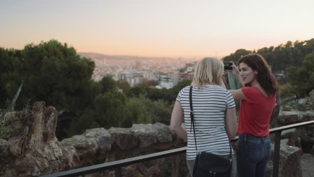 vídeos y material grabado en eventos de stock de young adult women admiring view and take picture on mobile phone in barcelona - menos de diez segundos