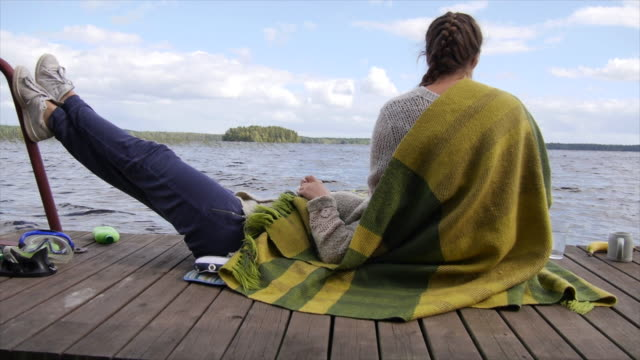 Young adult women girls relax on a lake dock. - Slow Motion