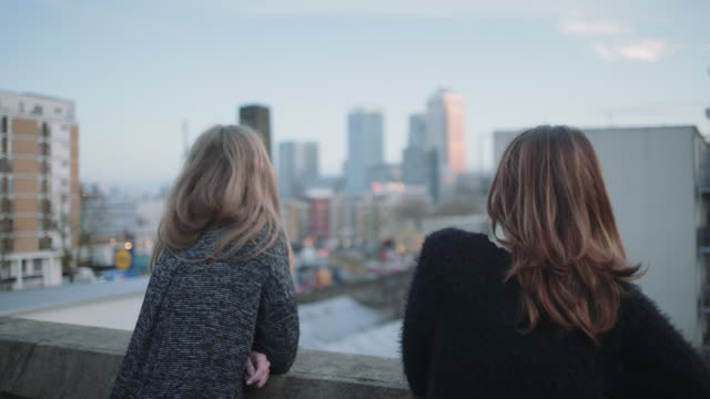 Young adult women looking out on rooftop