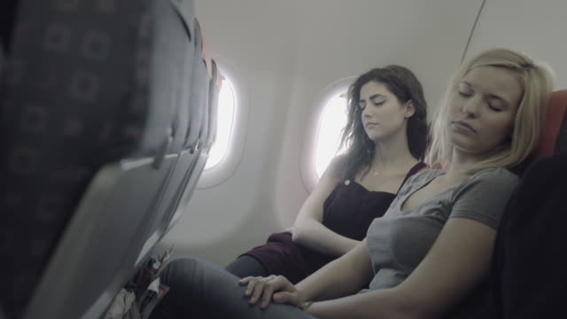 Young adult women on airplane sleeping