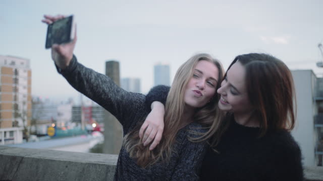 Young adult women taking selfie on mobile phone