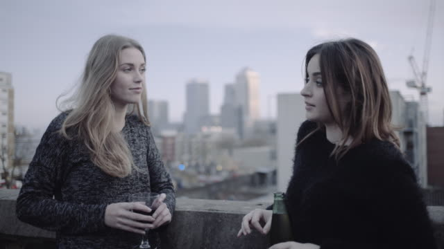 Young adult women talking and drinking on rooftop party