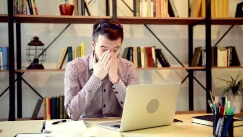 ung vuxen arbetar på en bärbar dator bloggare och gnuggar hans trötta ögon - journalist bildbanksvideor och videomaterial från bakom kulisserna