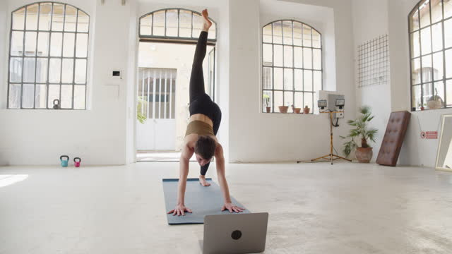 a young adult yoga teacher is doing an online video lesson with a laptop - pilates stock videos & royalty-free footage