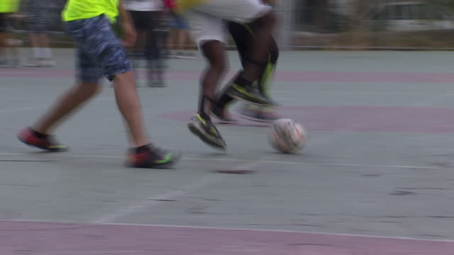 vídeos de stock, filmes e b-roll de young adults and children play football in a park in athens greece - passe de bola
