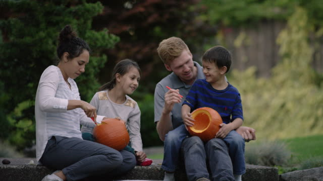 young adults carving pumpkins with children - carving craft product stock videos & royalty-free footage