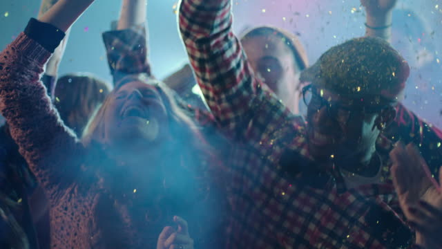 Young adults dance under glitter confetti in club medium (slo-mo)