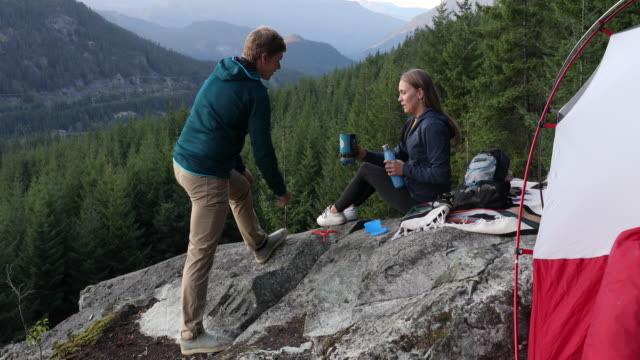 young adults enjoy camping experience, on rock slab above valley - sweatshirt stock videos & royalty-free footage