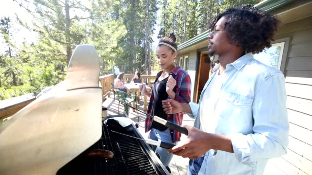 Young adults enjoy dancing while grilling outdoors