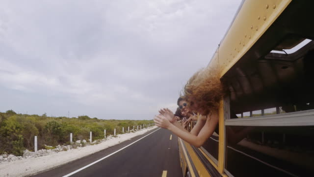 vídeos de stock e filmes b-roll de young adults hanging out of window of school bus - cool