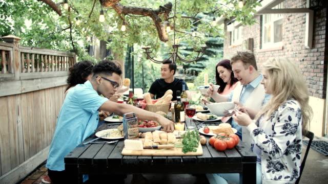 vídeos de stock, filmes e b-roll de os adultos novos têm o divertimento junto em um partido de jardim do verão - mesa de jantar