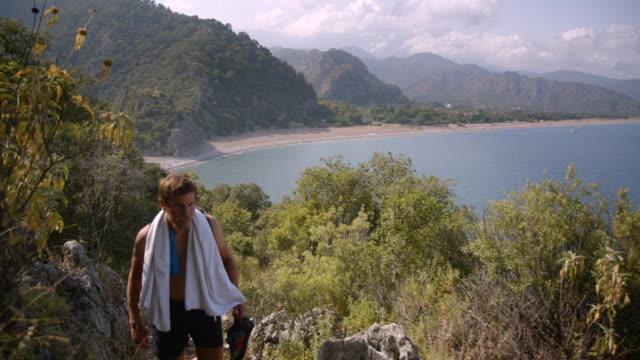 young adults hike near ocean coastline - olympos, turkey - asciugamano video stock e b–roll