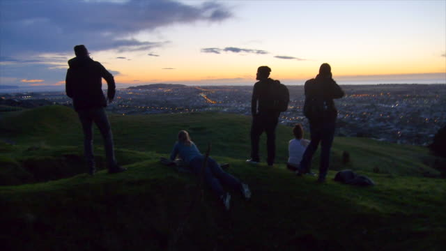 young adults hiking above a city at sunset. - slow motion - adventure stock videos & royalty-free footage