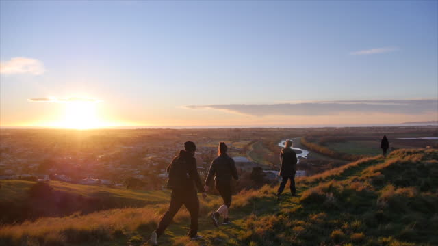 Young adults hiking above a city at sunset. - Slow Motion