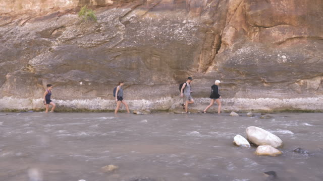 4K UHD: Young Adults Hiking Through a River