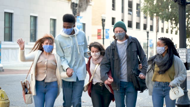 young adults hurry across city street wearing face masks - walkable city stock videos & royalty-free footage