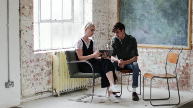 stockvideo's en b-roll-footage met young adults in a meeting in a creative studio with a digital tablet - loft apartment