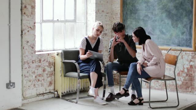 vídeos de stock, filmes e b-roll de young adults in a meeting in a creative studio with a digital tablet - armação de janela