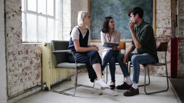 Young adults in a meeting in a creative studio with a digital tablet