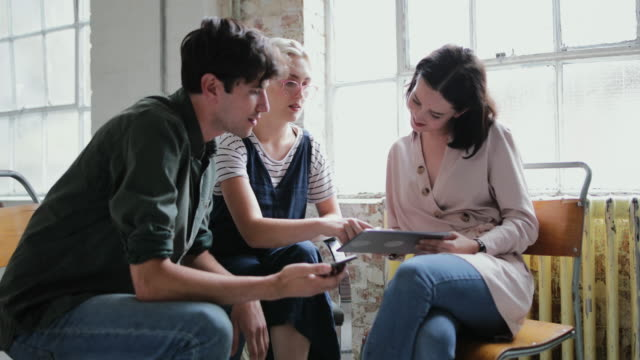 vídeos de stock e filmes b-roll de young adults in a meeting in a creative studio with a digital tablet - loft apartment