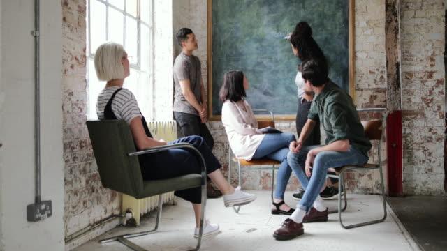 vídeos de stock, filmes e b-roll de young adults in a meeting in a creative studio writing on a blackboard - armação de janela
