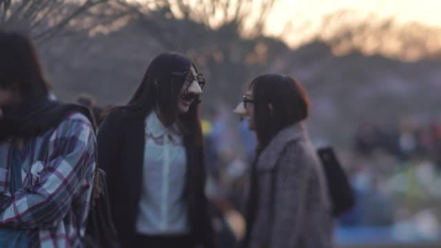 young adults laugh in yoyogi park - tokyo, japan - 扮装点の映像素材/bロール