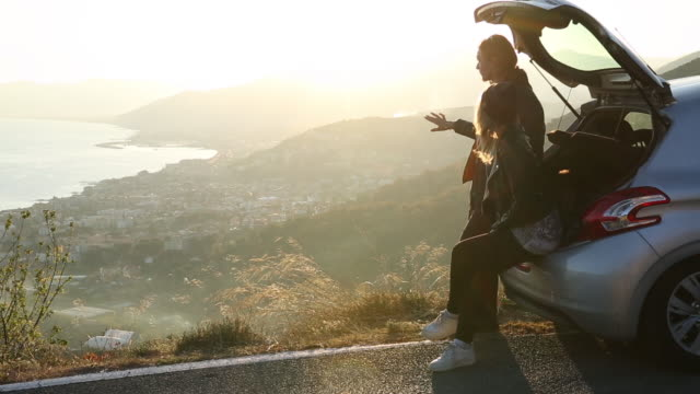 young adults meet on car tailgate, village & sea below - heckklappe teil eines fahrzeugs stock-videos und b-roll-filmmaterial