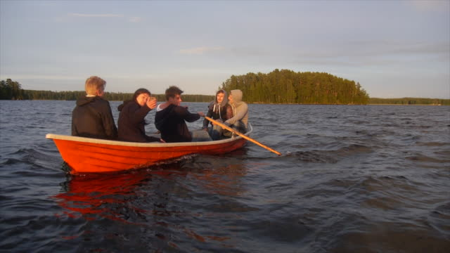 stockvideo's en b-roll-footage met young adults racing and rowing a boat on a lake at sunset. - slow motion - finland